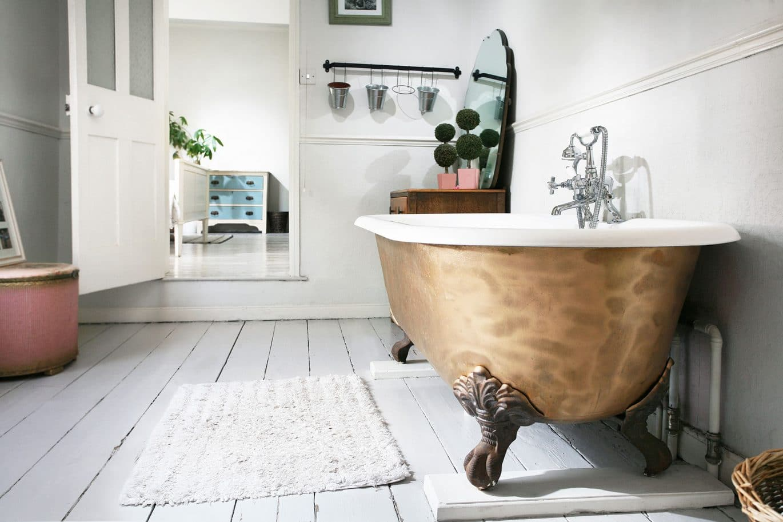 A clean modern Clear Interiors of Norwich customer bathroom with brass freestanding bath