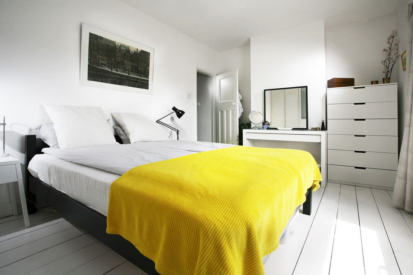 A clean and tidy customer bedroom with vibrant yellow bedspread in Norwich