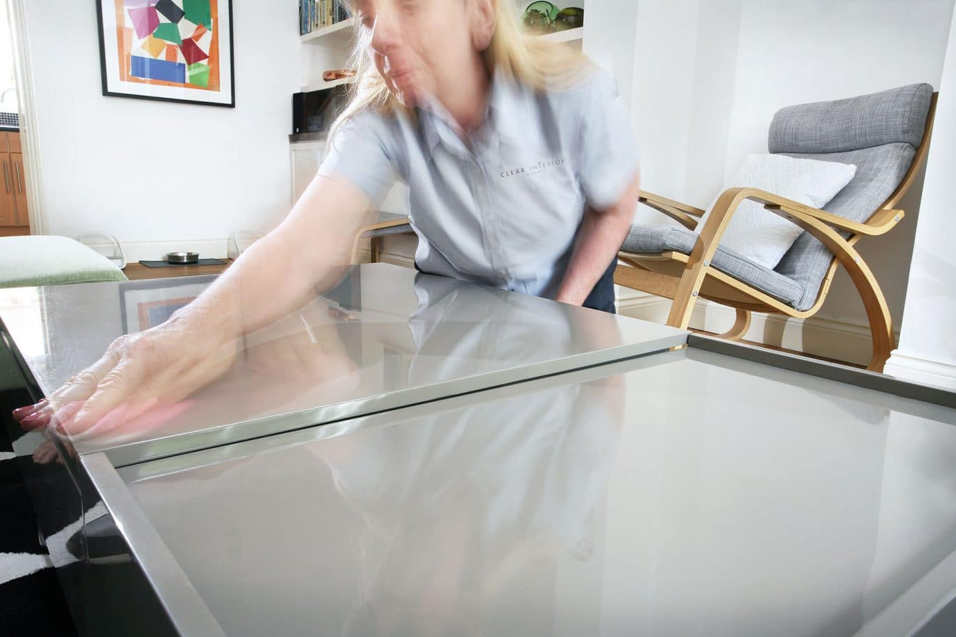 Clear Interiors of Norwich domestic cleaner is wiping a grey coffee table in a customer's home