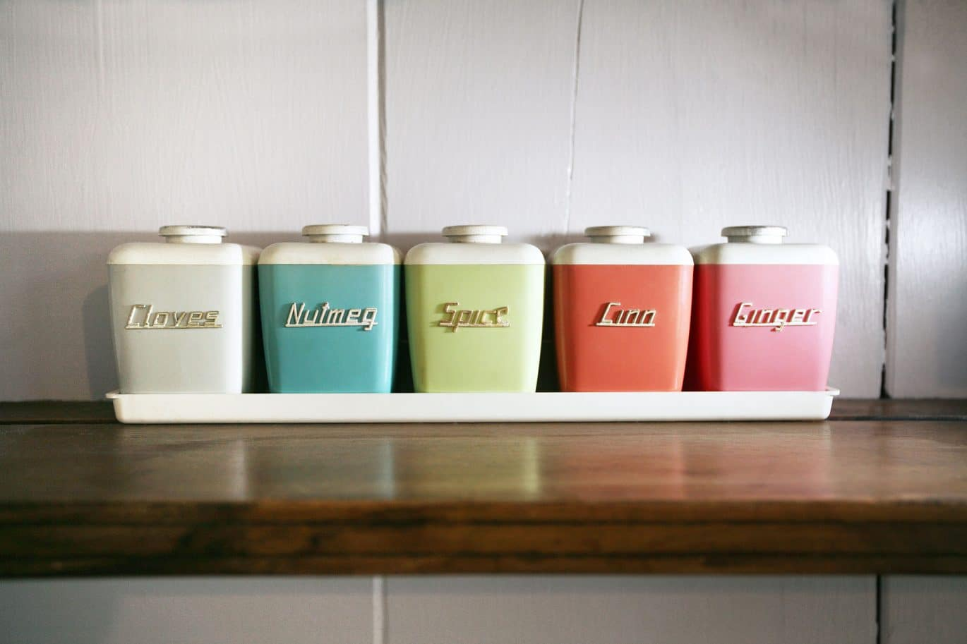 Close up of cleaning customers retro multicoloured spice jars