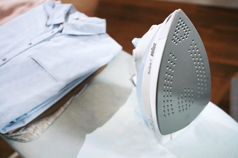 Iron on an ironing board next to neatly folded shirts