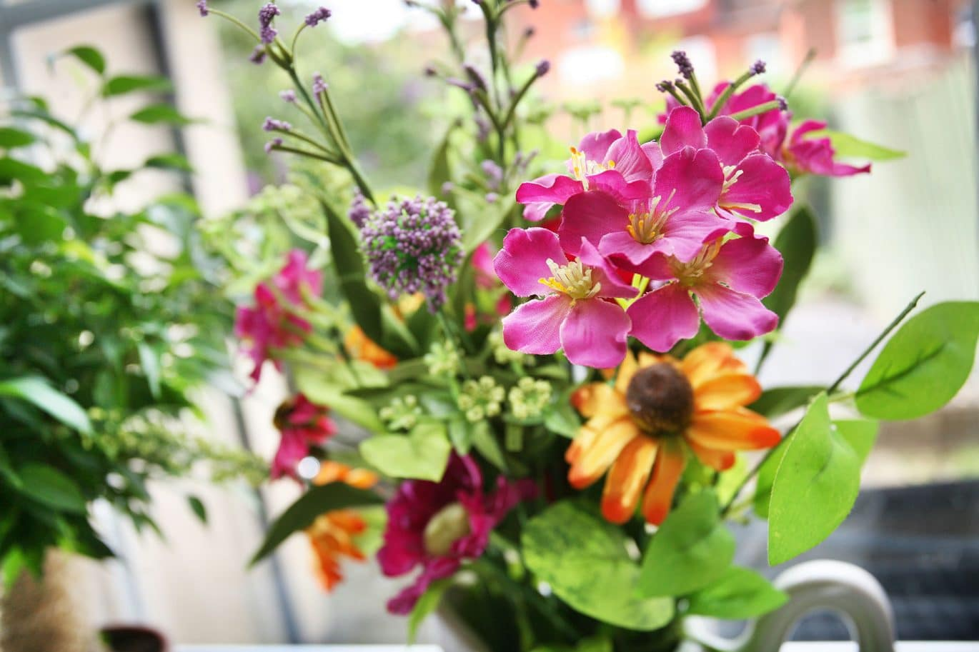 Close up of a bright flower arrangement on the windowsill in a clean customer's kitchen