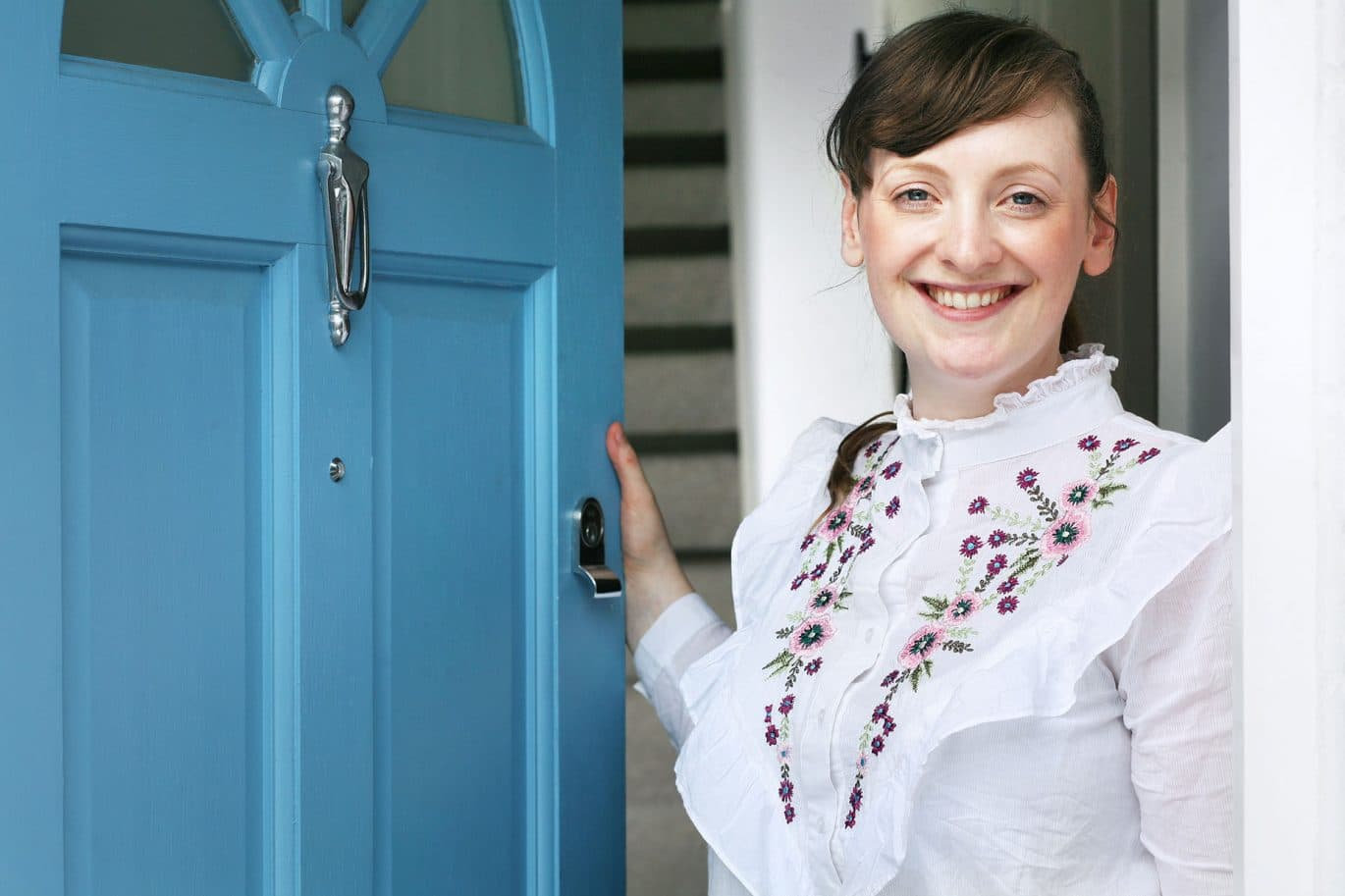 A Happy Clear Interiors of Norwich Cleaning Customer stands smiling at their front door